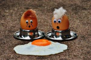 Protein - Zwei gekochte Eier mit Haaren schauen erschrocken auf ein Spiegelei auf dem Boden