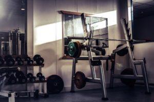 Ein Oldschool Fitnessstudio mit einem Powerrack, einer Langhantel, vielen Kurzhanteln, mehreren Hantelscheiben und einem Spiegel