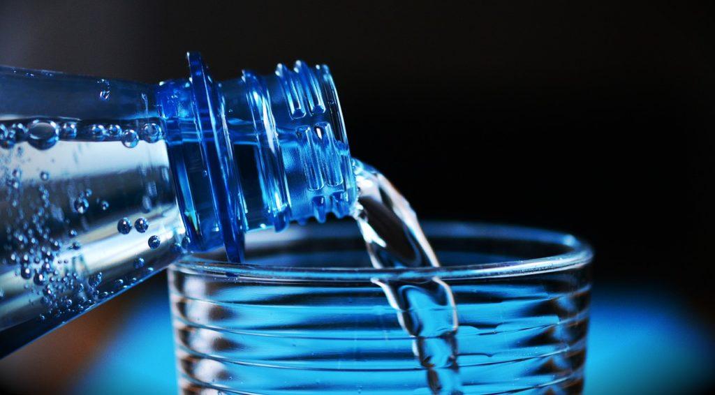 Wasser wird aus einer Flasche aus Plastik in ein Glas gegossen (Viel Trinken: Sport bei Hitze)