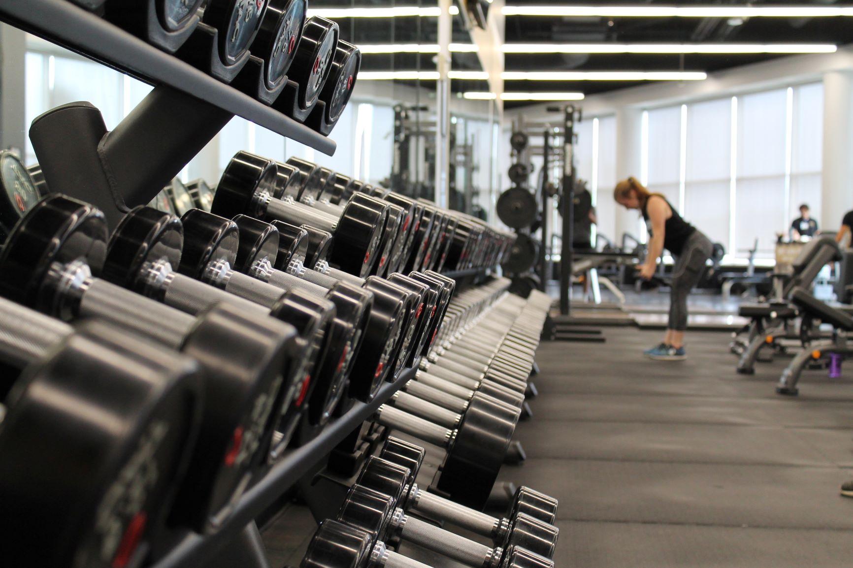 Bodybuilding Hanteln im Fitnessstudio, im Hintergrund trainiert eine junge Frau mit Hanteln.