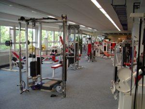 Fitnessstudio einer Fitnesskette, viele Maschinen mit rotem Bezug, Multipresse, Latturm etc.